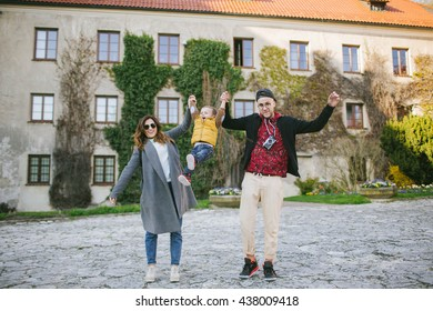 Happy young family on holiday, parents keep son's hands outdoors
