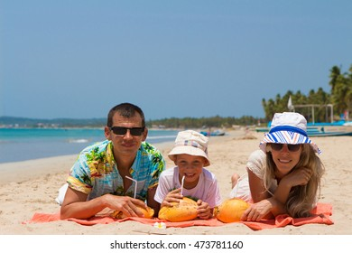 Happy young family on a tropical beach drink coconut