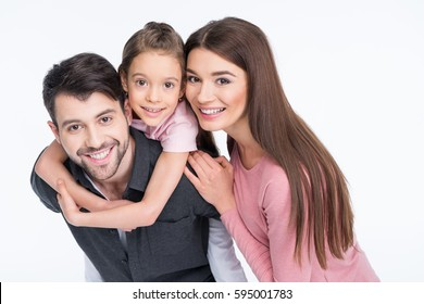 Happy young family with one child smiling at camera isolated on white
