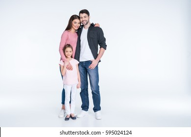 Happy young family with one child standing embracing and smiling at camera isolated on white