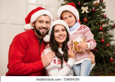 happy young family with one child holding christmas gift and smiling at camera