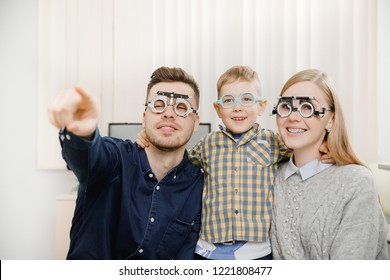 Happy young family at ophthalmologist appointment. Dad in denim shirt with dark hair shows direction of gaze index finger. Trendy little son and mom big blue eyes blonde looking Modern clinic