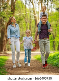 Happy young family parents with a child in a green summer city park have fun walking together