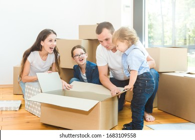 Happy young family, parents daughter and son, unpacking boxes and moving into a new home. funny kids run in with boxes