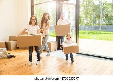 Glückliche junge Familie, Eltern Tochter und Sohn, packen Kisten aus und ziehen in ein neues Zuhause. lustige Kinder laufen in Kisten