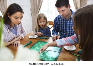 Happy young family plaing board game with two daughters