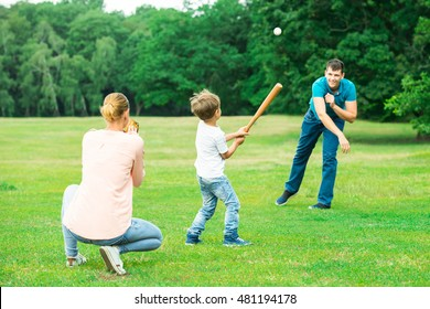 Happy Young Family Playing Baseball At Park
