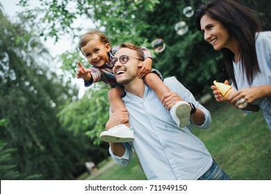 Happy young family playing with bubble wands with son sitting on fathers shoulders in park outdoors in summer