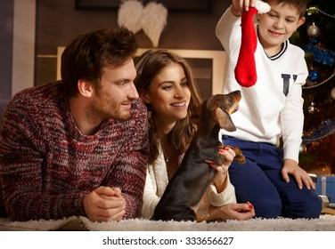 Happy young family playing with dachshund puppy receiving for christmas.