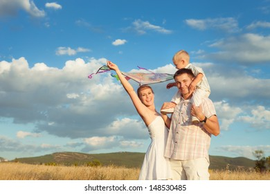 Happy young family playing with kite in summer. Family Vacation.