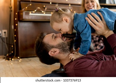 Happy young family playing on the floor  in the room