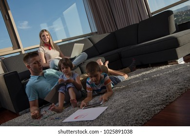 Happy Young Family Playing Together at home on the floor using a laptop computer and a children's drawing set
