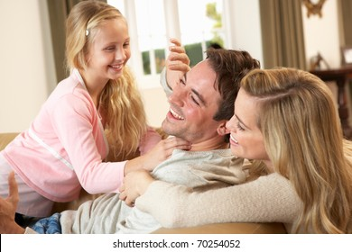Happy young family playing together on sofa