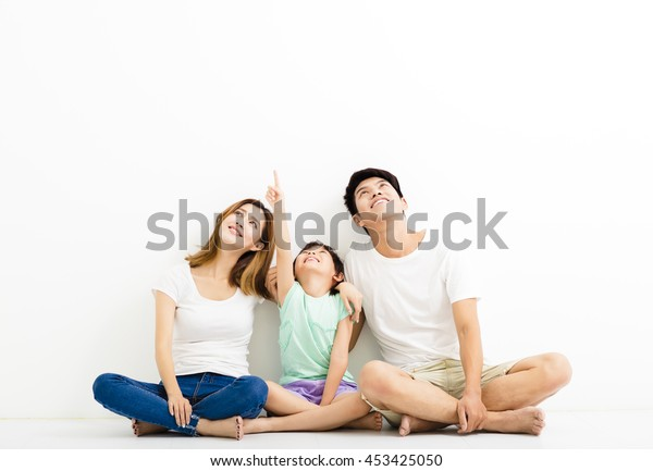 Happy  Young  Family pointing and looking up