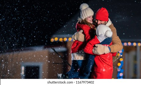 Happy Young Family Portrait in the Fallin Snow, Father Embraces Wife and Holds Daughter. Family Enjoys Winter Holiday in the Backyard of their Idyllic House Decorated with Garlands.