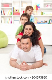 Happy young family portrait - parents and kids joyful heap at home