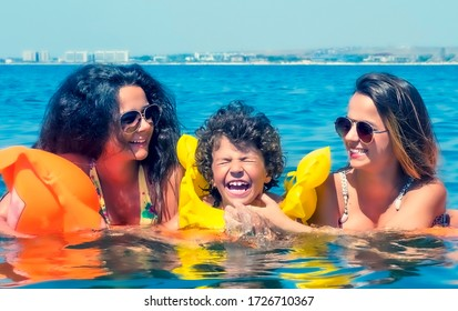 Happy young family positive mom and two little daughters swim on a yellow air mattress in the sea on a sunny summer day during vacation. Vacation concept abroad.