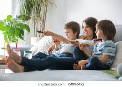 Happy young family, pregnant mother and two boys, eating tasty pizza at home, sitting on the sofa, watching TV and having a laugh
