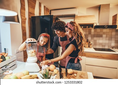 Happy young family is preparing healthy meal in the kitchen. Mother, father and daughter are putting slices of fruit in the blender and making fruit smoothie.