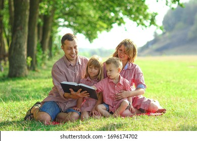 happy young family reading the Bible in nature