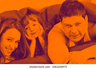 happy young family relaxing in bed duo tone