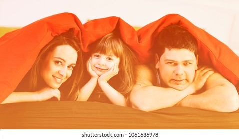 happy young family relaxing in bed