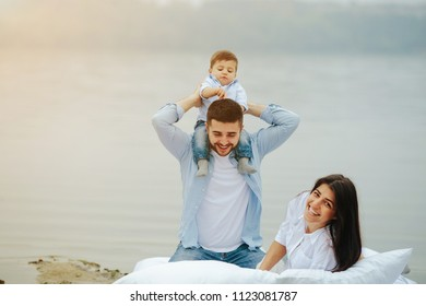 Happy young family relaxing together on the lake. They lie on a white mattress with pillows