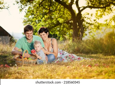 Happy and young family relaxing together in summer nature