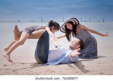 Happy young family relaxing together on the beach,people having fun on summer vacation.