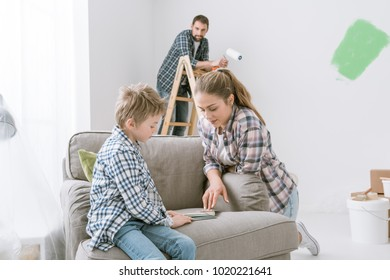 Happy young family renovating and decorating their home, the boy is picking colors swatches with his mother and his father is painting on the background