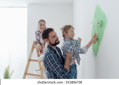 Happy young family renovating their home, the father is holding his son and he is helping him to paint a wall with a paint roller, the mother is standing on the ladder and smiling