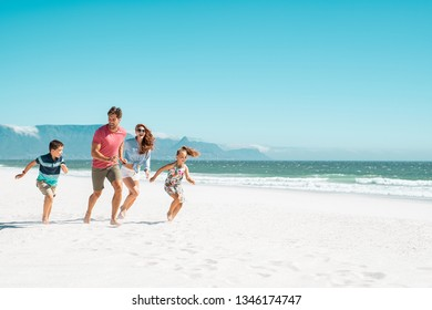 Happy young family running on the beach with copy space. Beautiful mother and laughing father enjoying summer vacation with son and daughter. Smiling parents with two children in casual having fun.