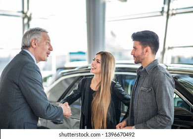 Happy young family shaking hands to the salesman and choosing their new car in a showroom
