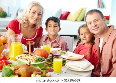 Happy young family sitting at celebration table on Thanksgiving Day and looking at camera