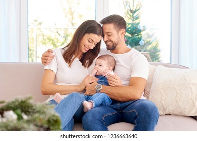 Happy young family sitting on sofa with their baby girl and enjoy each other's company at Christmas time.