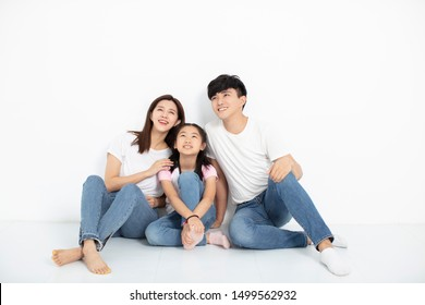 Happy Young family Sitting On Floor Looking Up