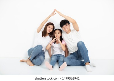 happy young family sitting on floor with home concept