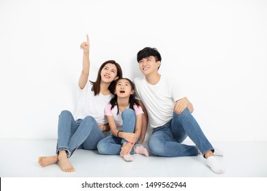 happy young family sitting on floor and looking up