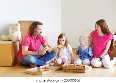 Happy young family sitting on a floor and eating pizza in their new home
