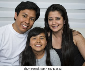 Happy young family sitting on sofa.