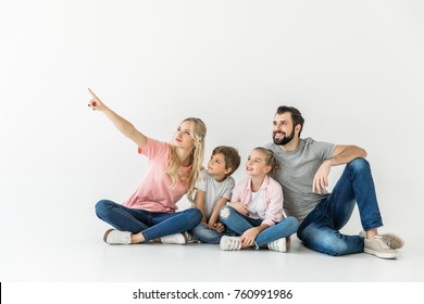 happy young family sitting together and looking away isolated on white