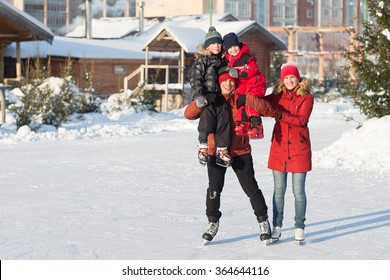 Happy young family skate at the rink in the winter. Beautiful family walking and playing on the ice in winter.