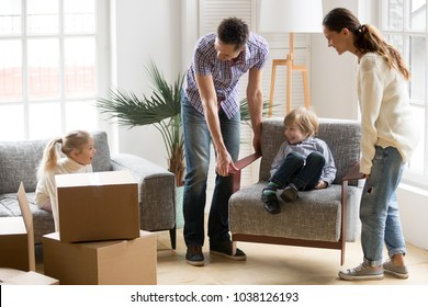 Happy young family with small kids having fun together playing on moving day in new home concept, father and mother carry little son on chair while excited daughter sitting on sofa unpacking boxes