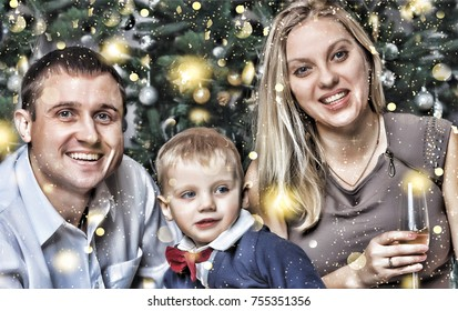 Happy young family with a small son happily smiling meets the new year at home. Christmas tree, decorations and gifts. New Year Christmas.