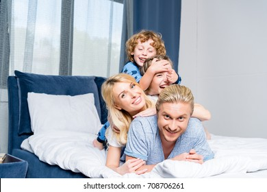 happy young family smiling at camera while lying together in bed