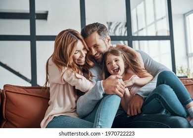 Happy young family smiling and embracing while bonding together at home - Shutterstock ID 1970722223