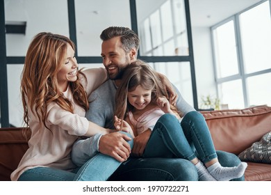 Happy young family smiling and embracing while bonding together at home - Shutterstock ID 1970722271