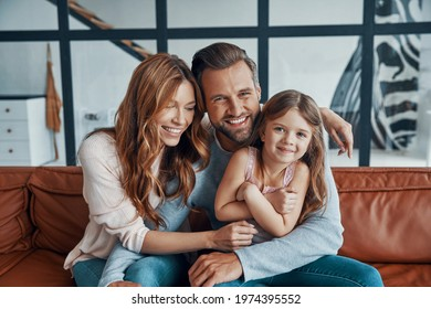 Happy young family smiling and looking at camera while bonding together at home - Shutterstock ID 1974395552