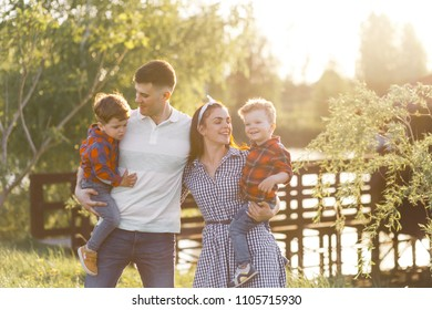 Happy young family spending time together outside in green nature near the wate. Parents playing with twins outside. Family of four walkng  at the sunset hugging and having fun