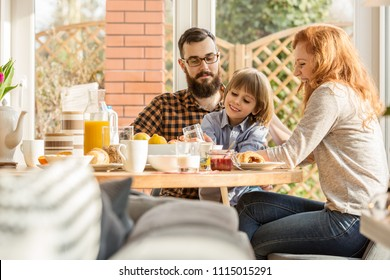 Happy, young family spending time together, eating a meal in an arbor